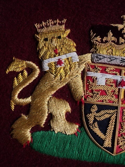Hand embroidered Royal coat of arms British UK Royal coat of arms – handmade Bullion gold and silver wire embroidered on Maroon felt background . Coat of arms available with beautiful frames / without frame